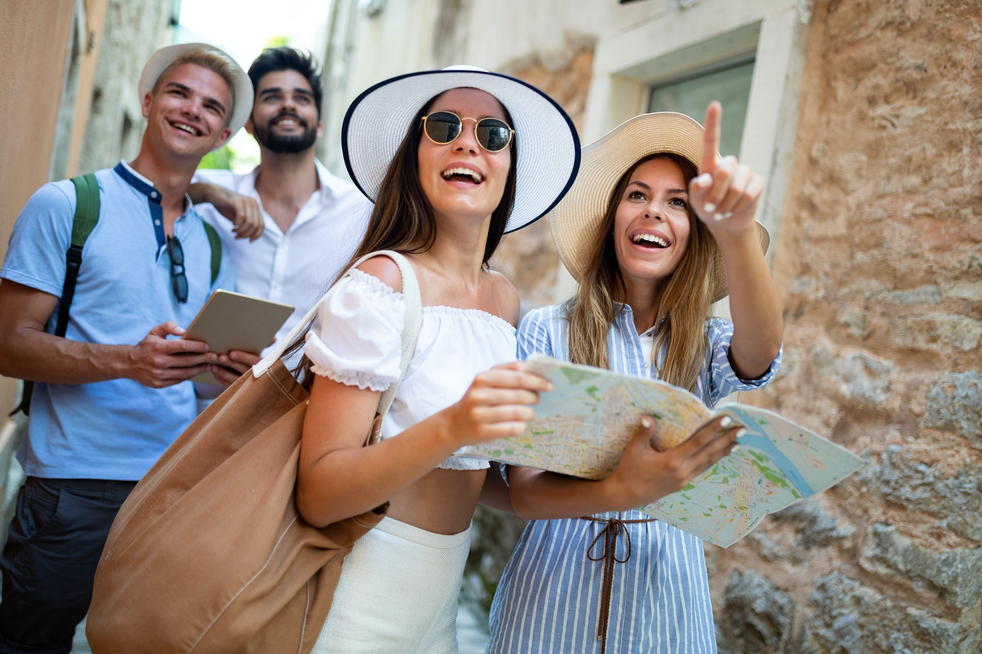 Group of friends tourists with map in old city on vacation